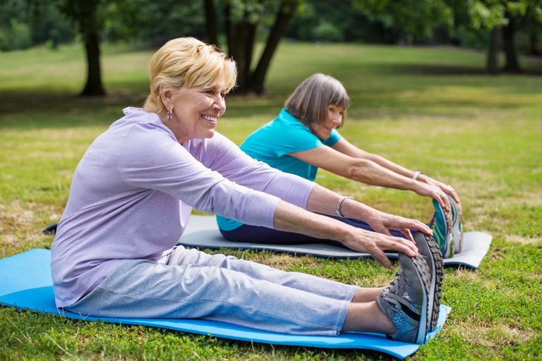 Two senior women doing stretching exercise in park