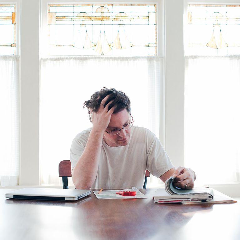 Man struggles with paperwork at desk.