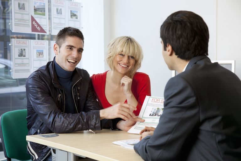 couple showing real estate listing to agent