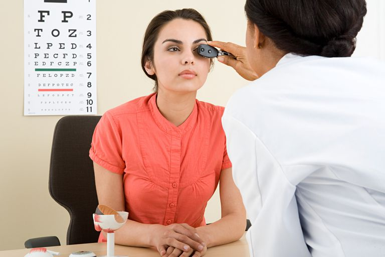 a woman having her eyes examined by a doctor