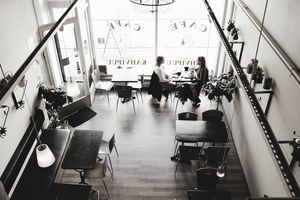Overhead view of a cafe with customers conversing.