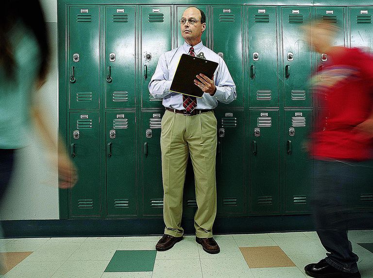Man in school hallway with clipboard