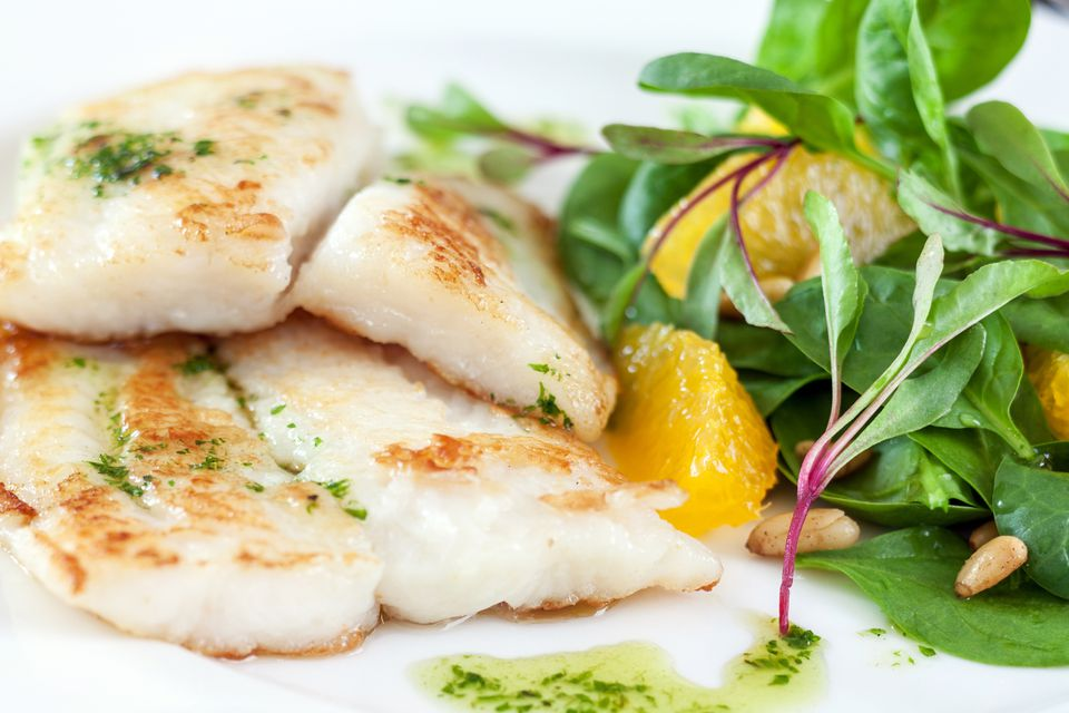Fillet of white fish with spinach, orange, pine nuts and olive oil .