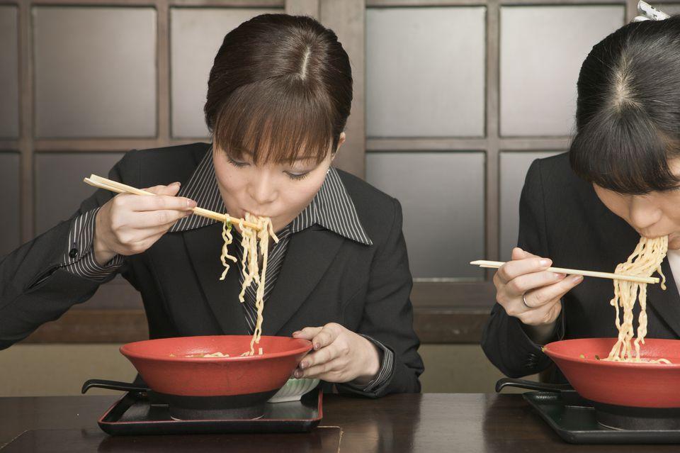 Two Businesswomen Eating Noodles in Restaurant