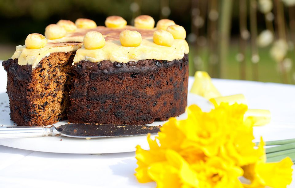 Fruit cake topped with a yellow marzipan layer and round balls of marzipan