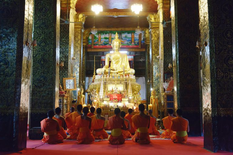 Monks and novices praying in buddhist temple, Luang Prabang, Laos