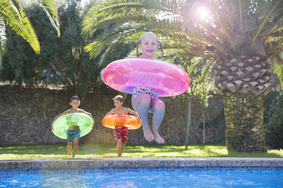Kids on vacation jumping into pool with inner tubes
