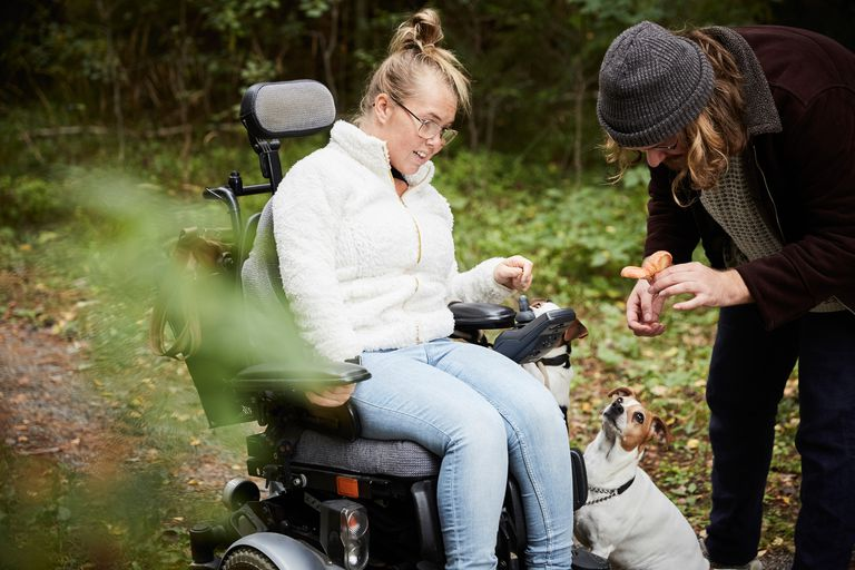 Disabled woman in wheelchair looking at caretaker holding mushroom in forest