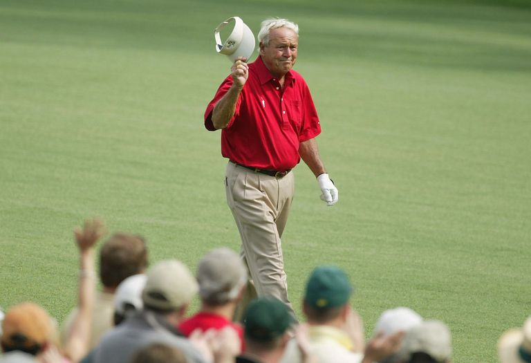 Arnold Palmer waves to the crowd during the second round of the Masters at the Augusta National Golf Club on April 9, 2004