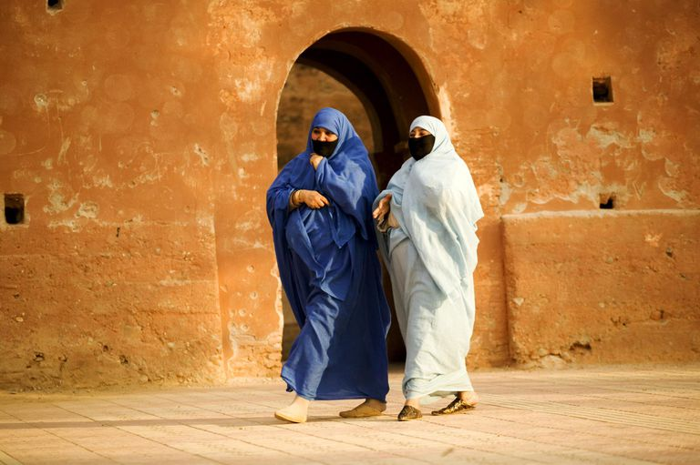 Two Muslim women wearing the traditional chador or nikab (full body cloak) walking past the ramparts that surround the medina in the town of Taroudannt, Morocco. (MR)