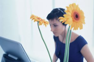 Flower in front of a young woman wearing headset at the computer