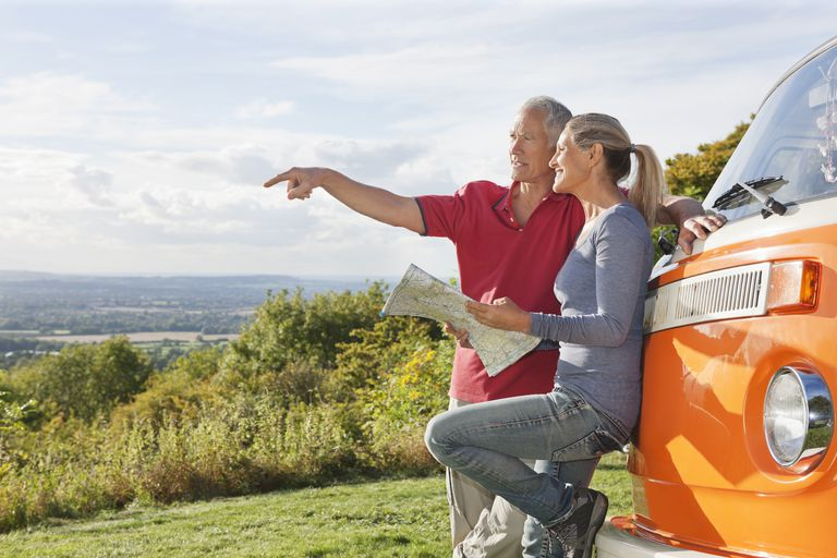 Couple looking at map by camper van