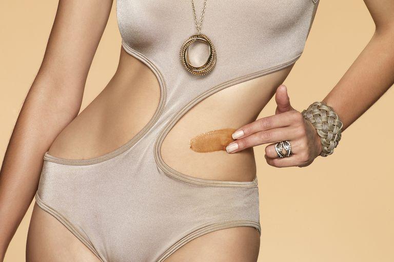 Woman in swimsuit using bronze sun cream