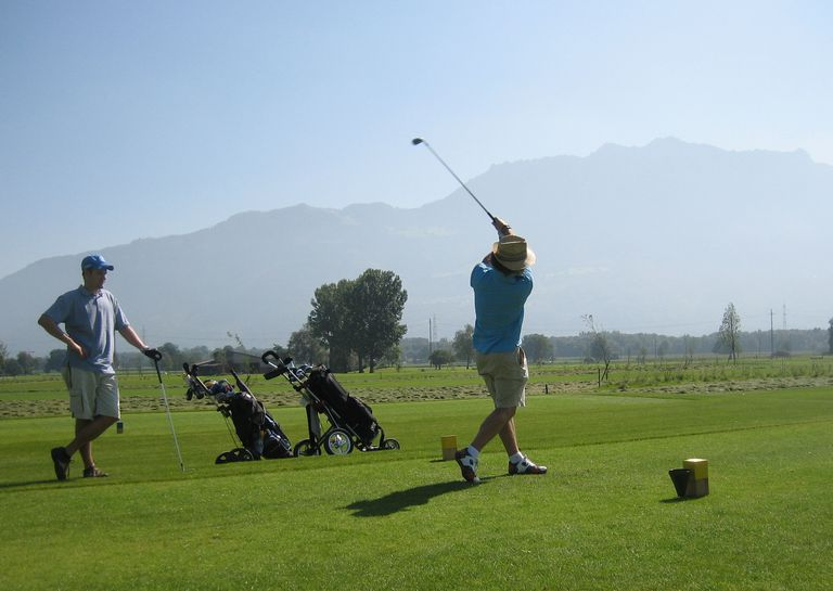 Two golfers teeing off.