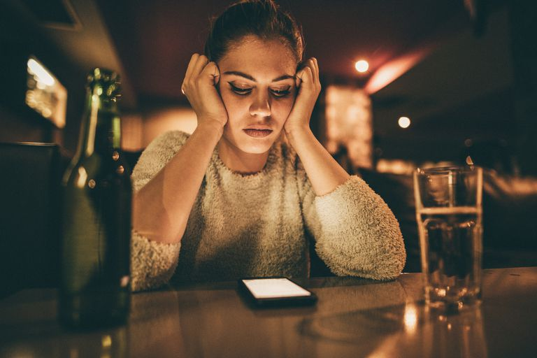 upset woman looking at cell phone on bar