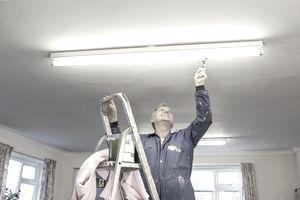 maintenance man fixing overhead light in office