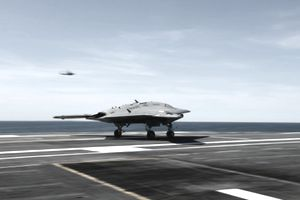 An X-47B unmanned combat air system conducts a touch and go landing.