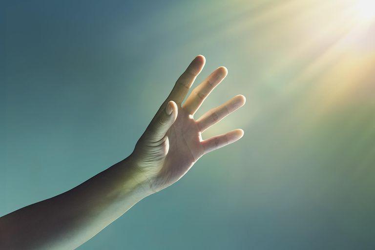 Hand reaching towards glowing light from corner