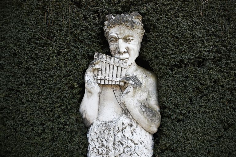 Stone statue of Greek god Pan set in yew (Taxus) hedge, Winter