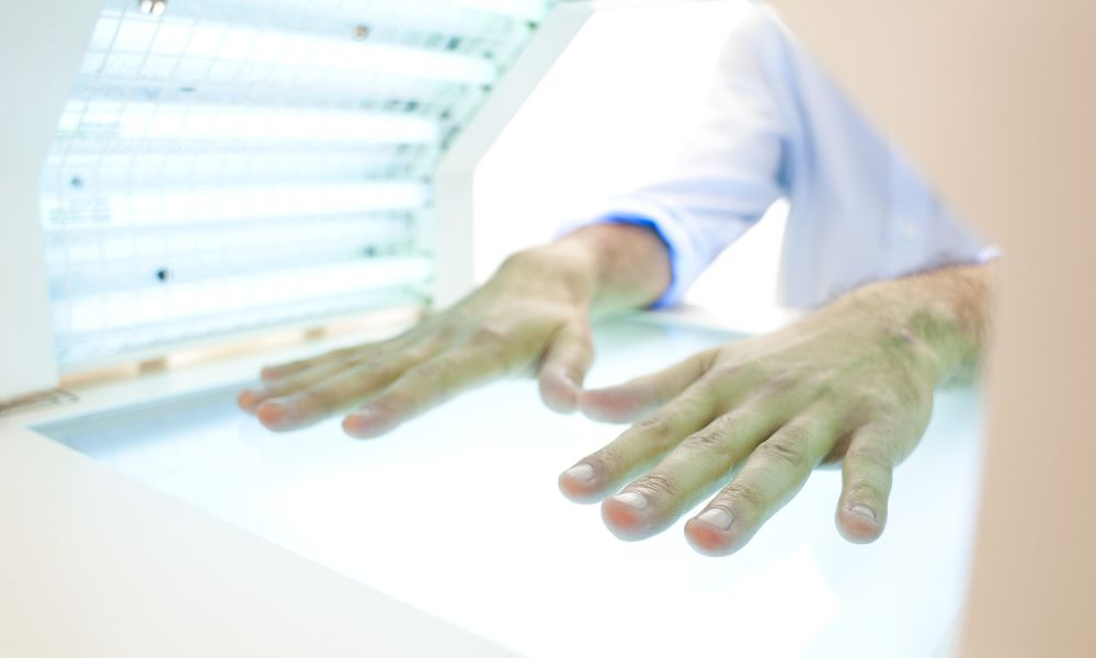 Man's hands in phototherapy booth