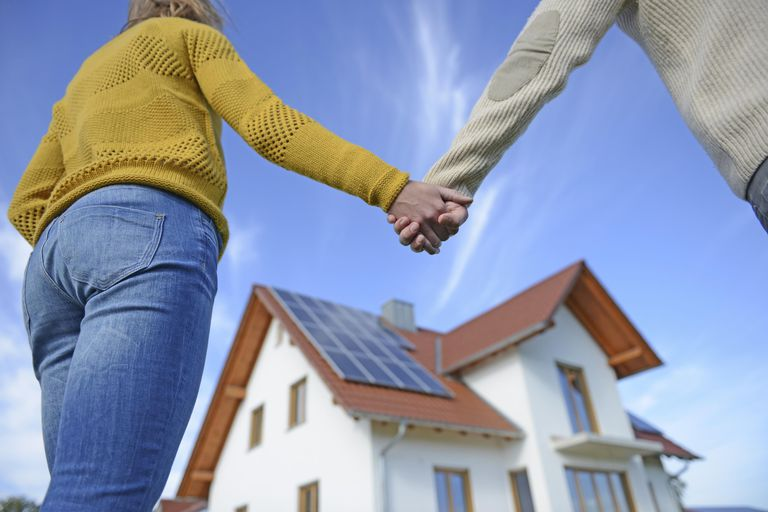 Couple holding hands in front of new home, low angle view