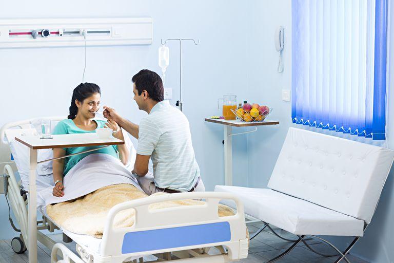 man feeding pregnant woman in hospital bed