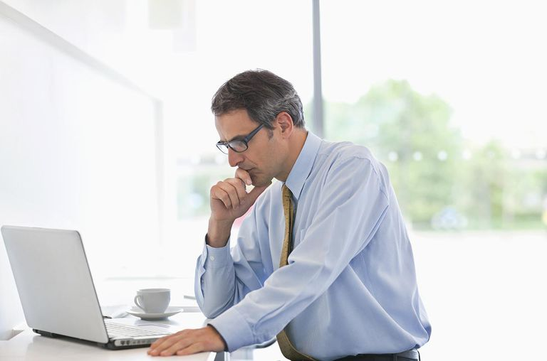 Businessman working on laptop and coffee cup in office cafeteria