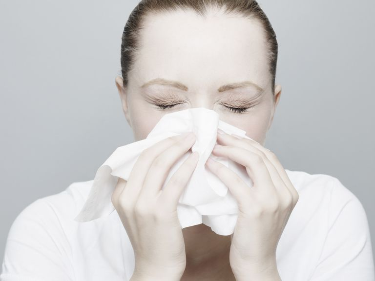 Woman Sneezing and Blowing Nose With White Tissue.