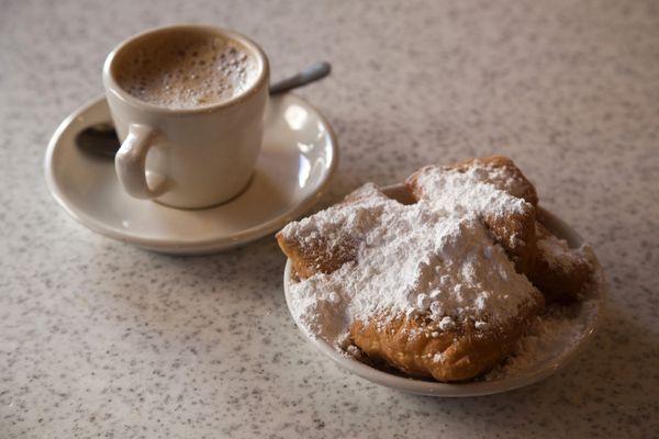 Beignets and cafe au lait at Cafe Du Monde, French Quarter, New Orleans, Louisiana, USA