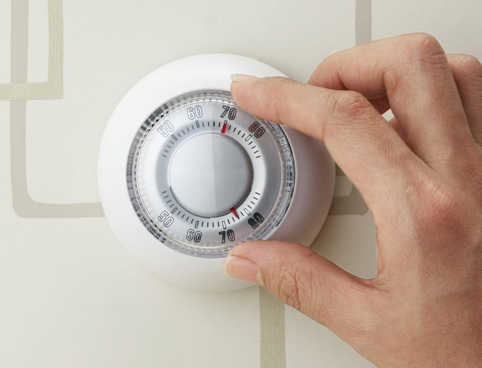 Hand turning dial on thermostat