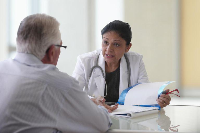 Doctor Explaining Paperwork To Senior Patient