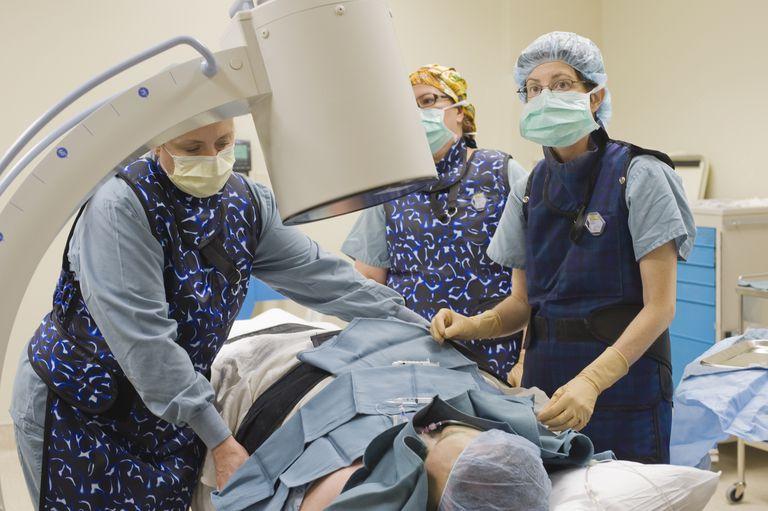 Surgeon and team position patient under xray machine