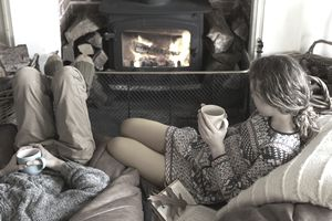 Two people drinking cups of tea by the fireplace