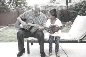 older man teaching child to play guitar