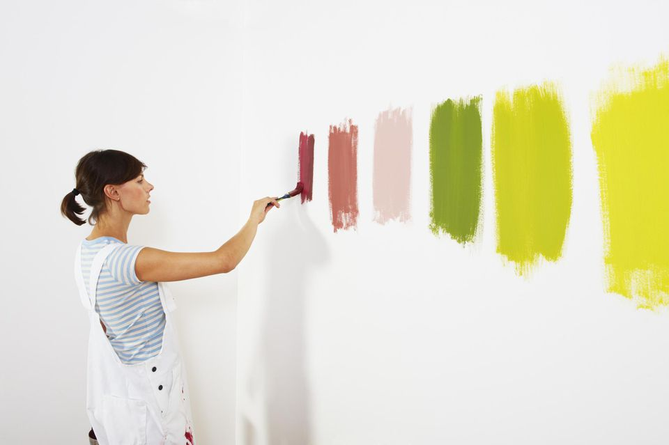 Woman painting color swatches on wall