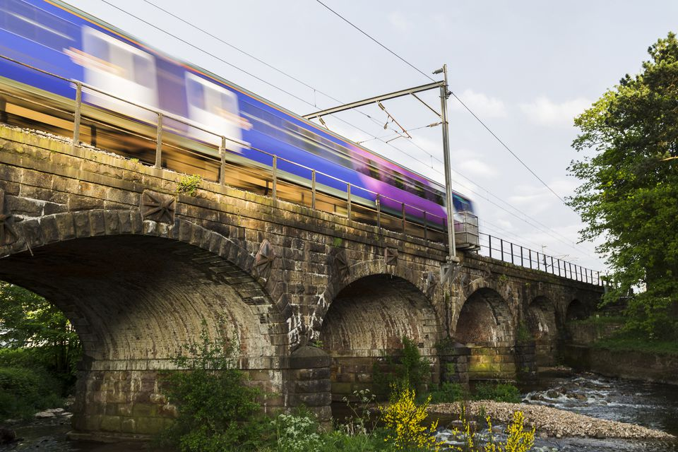 A local train passes over the arches of the Six Arches caravan site at Scorton, Lancashire