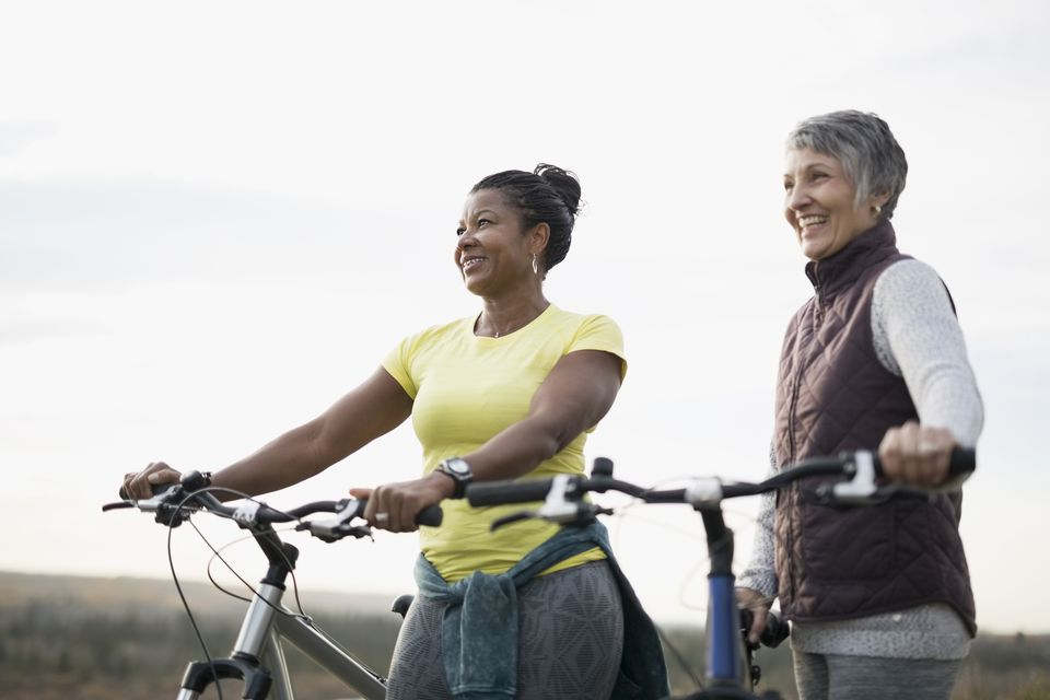Smiling women with bicycles looking away