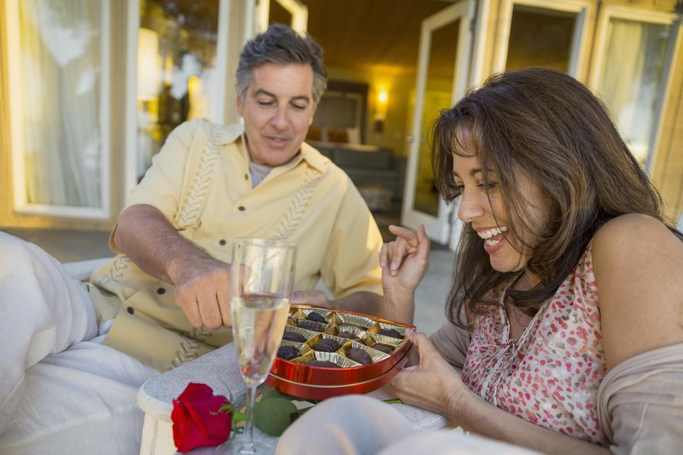 Smiling mature couple celebrating anniversary with chocolates and champagne on patio