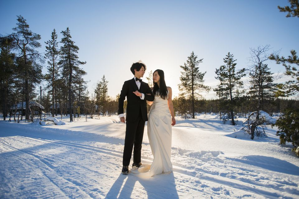 A married couple stand at snow field