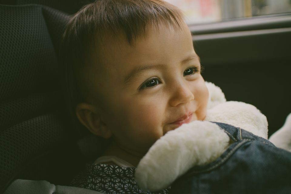 Happy adorable baby girl in car