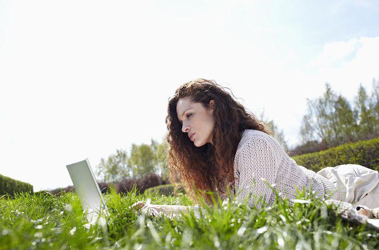 Woman using laptop in meadow