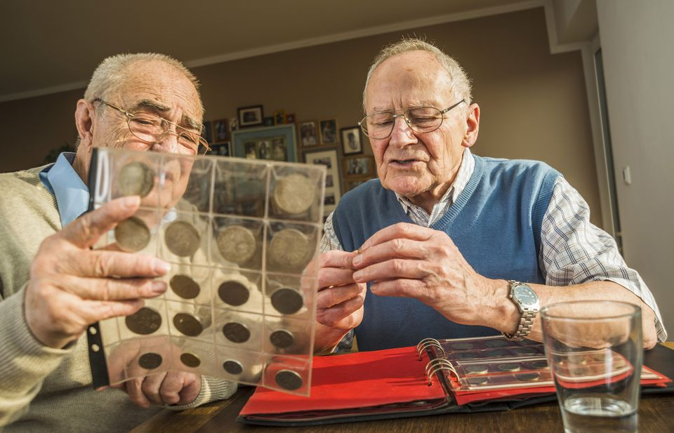 Two senior friends with coin album