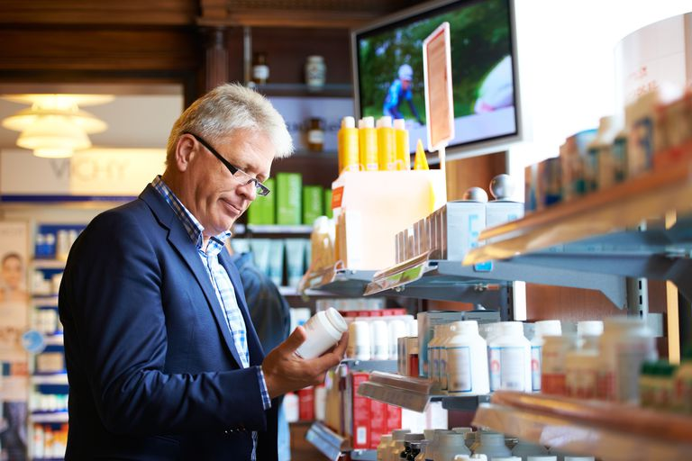 man looking at supplement bottle in store