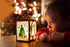 young boy looking at Christmas decoration with lit-up tree in background