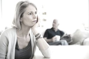 stressed mature woman with man in background