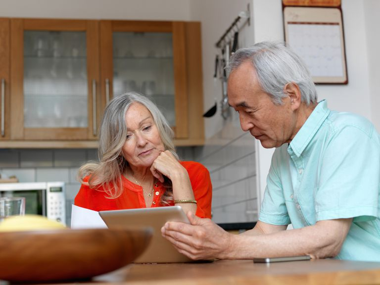 Older couple looking at stock allocation on tablet in kitchen.