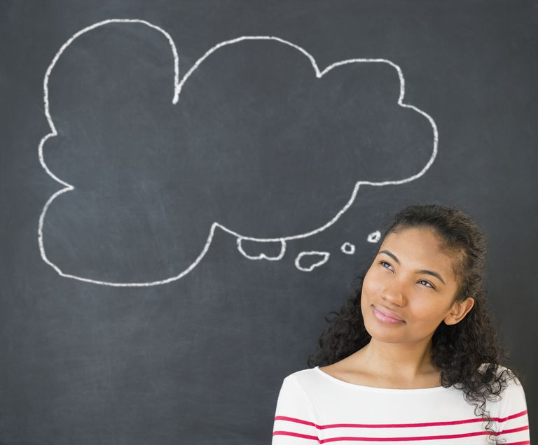 Mixed race woman under thought bubble on chalkboard