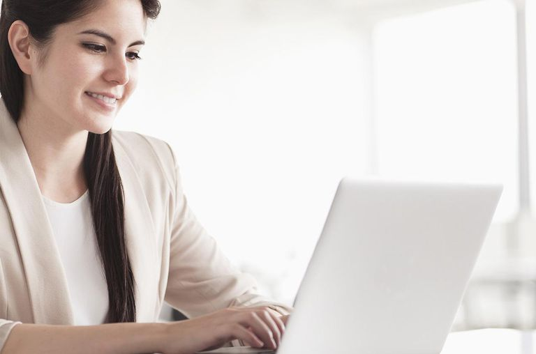 Smiling young businesswoman using her laptop
