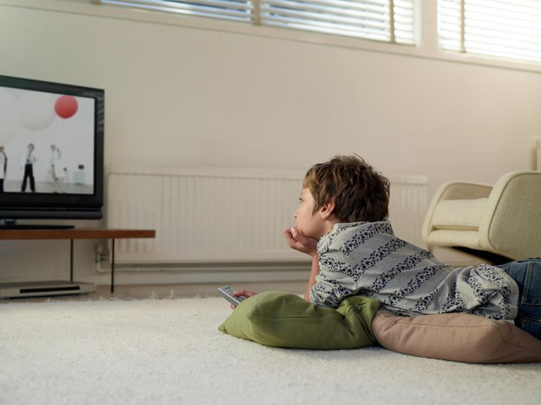 Boy lying on floor at home watching TV