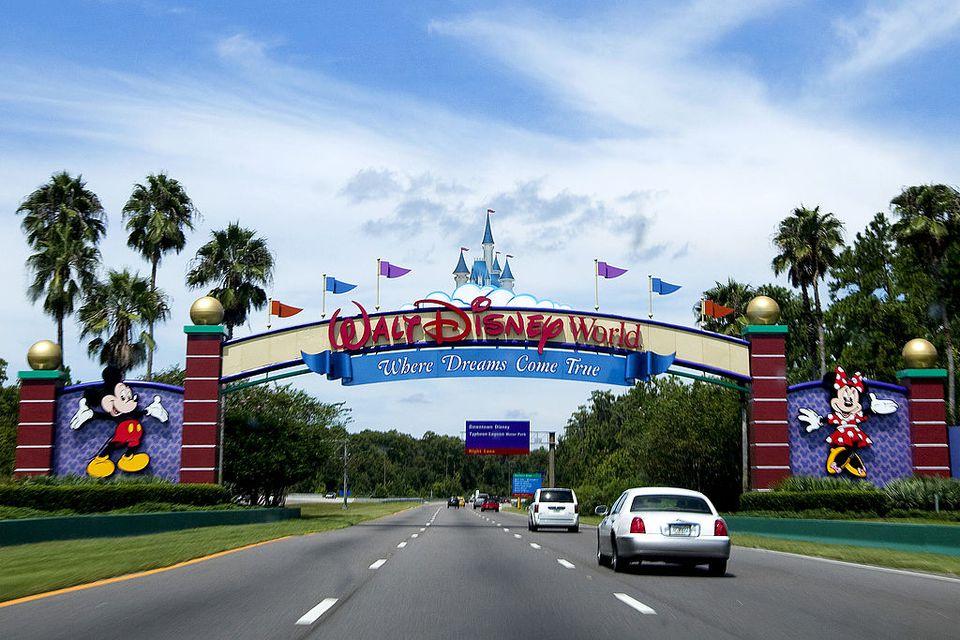 Automobiles driving under entrance sign to Walt disnye World.